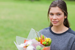 Young calm girl holding a bunch of flowers Stock Image