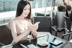 Young calm girl holding cellphone and looking at the screen. End of conversation. Young calm pleasant girl spending time in the restaurant holding her cellphone Stock Photography