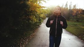 Young calm man in black jacket walking in the autumn park stock video