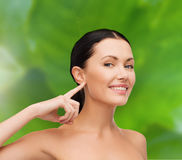 Young calm woman pointing to her ear Royalty Free Stock Photos