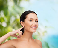 Young calm woman pointing to her ear Royalty Free Stock Photography