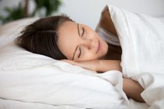 Young calm woman sleeping well alone on soft pillow stock images