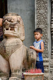 Young Cambodian boy waiting outside a temple with statue Stock Photography