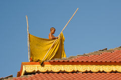 Young Cambodian monk is helping in the building of the roof of a temple Stock Photography