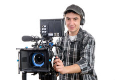 Young cameraman with movie camera. On the white background Stock Photos