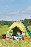 Young camping couple cooking meal outside tent. In sunny countryside royalty free stock photos