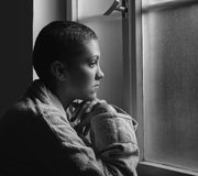 Young cancer patient in front of hospital window. Young cancer patient standing in front of hospital window Stock Image