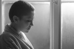 Young cancer patient in front of hospital window Stock Photo