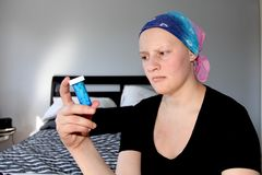 Young cancer patient in a headscarf looks at pill bottle in concern. Young cancer patient in a headscarf looks at chemotherapy Royalty Free Stock Photo