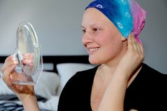 Portrait of a young cancer patient in a headscarf looking at self in mirror and smiling royalty free stock photography