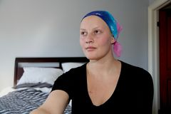 Portrait of a young cancer patient in a headscarf looks off to side. Young cancer patient in a headscarf Stock Photo