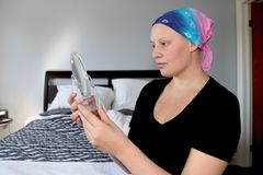 Portrait of a young cancer patient in a headscarf looking at self in mirror Royalty Free Stock Photo