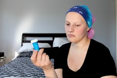 Portrait of a young cancer patient in a headscarf looks away from bottle of pills she is holding Stock Image
