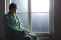 Young cancer patient sitting in front of hospital window Stock Images