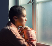 Young cancer patient standing in front of hospital window Royalty Free Stock Photo