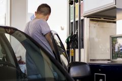 Young car driver man in casual on fuel station near gas pump stock images