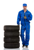 Young car mechanic with pile car tires. Showing thumbs up Royalty Free Stock Photos