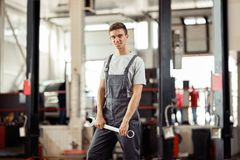 A young car mechanic is standing with a monkey wrench in his hands royalty free stock image
