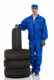 Young car mechanic with tires for the car Stock Photos