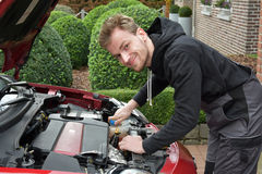 Young car mechanic at work. Young car mechanic has opened engine hood and inspects the automobile stock photography