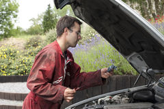 Young car mechanist checking the oil Royalty Free Stock Images