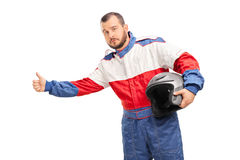 Young car racer holding a helmet and hitchhiking Stock Photography