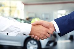 Young car salesman shaking hands with client in dealership. Closeup stock images