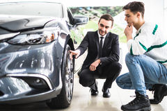 Young car salesman showing the advantages of the car to the customer and tires. Stock Photography