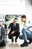 Young car salesman showing the advantages of the car to the customer and tires. Royalty Free Stock Photo