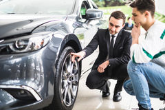 Young car salesman showing the advantages of the car to the customer and tires. Royalty Free Stock Photos