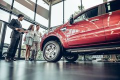 Young car salesman standing at the dealership telling about the features of the car to the customers. Buying their first car together. Bottom view of young car royalty free stock images