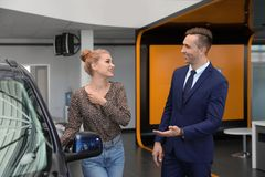 Young car salesman working with client. In dealership stock photography