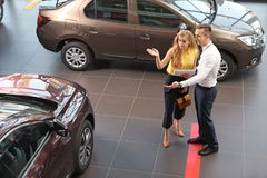 Young car salesman working with client. In dealership stock photo