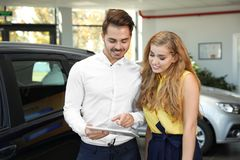 Young car salesman working with client. In dealership royalty free stock image