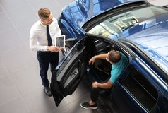 Young car salesman working with client. In dealership stock photos