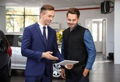 Young car salesman working with client. In dealership royalty free stock photography