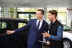 Young car salesman working with client. In dealership stock image