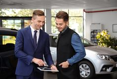 Young car salesman working with client. In dealership royalty free stock photo