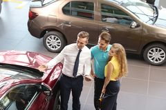Young car salesman working with clients. In dealership royalty free stock photo