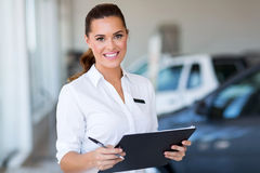Young car saleswoman. Holding clipboard in showroom royalty free stock photos