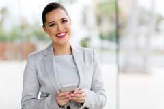 Young career woman. Beautiful young career woman using cell phone in office Royalty Free Stock Image