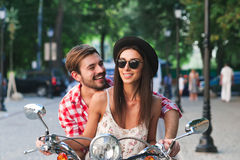 Young and carefree couple learning to drive a scooter Royalty Free Stock Images