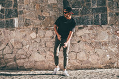 Young and carefree. Full length of handsome young African man in casual clothes moving and gesturing while standing against the stoned wall outdoors Royalty Free Stock Photography