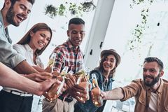 Young and carefree. Group of young people in casual wear toasting each other and smiling while having a dinner party royalty free stock image