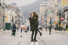 Young carefree happy people. Caucasian young students. Guy and girl. Love. Walk together on the european street in winter road. royalty free stock photo