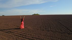 Young carefree woman in red dress turning around standing at plowed field. Happy beautiful woman in long red dress is standing and turning around herself on a stock video footage