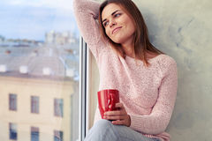Young carefree youth stretches on the windowsill while looking t stock photo