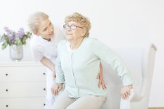 Young caregiver assisting smiling lady Stock Photos