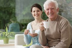 Young caregiver and elderly male Stock Photo