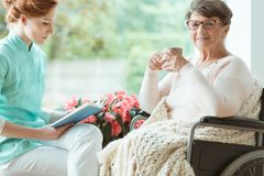Pensioner with osteoporosis in wheelchair. Young caregiver reading a book out loud to pensioner on wheelchair sick on osteoporosis stock photography